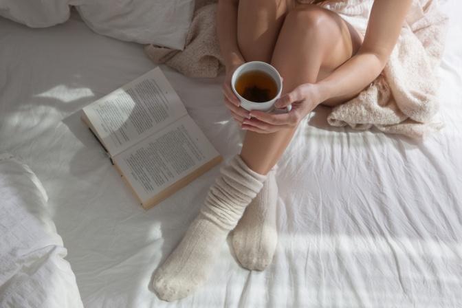 Frau mit einer Tasse Tee und einem Buch im Bett