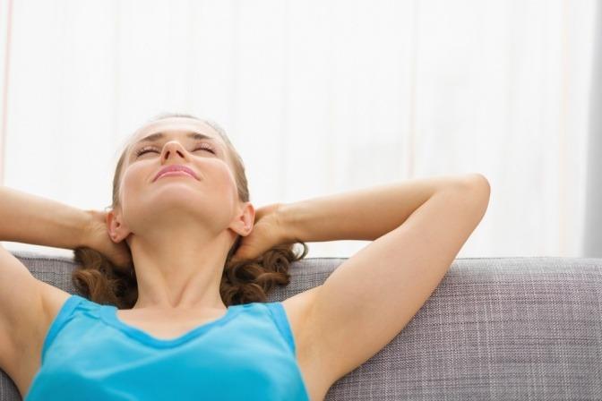 Eine Frau ist entspannt auf einem Sofa