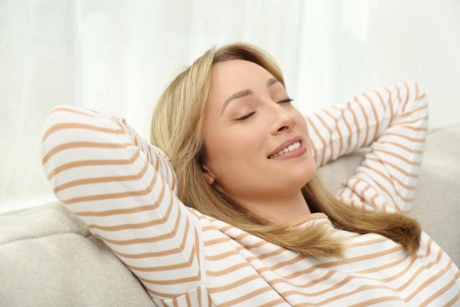 Eine entspannte Frau mit verschränkten Armen hinter dem Kopf und geschlossenen Augen sitzt auf dem Sofa.