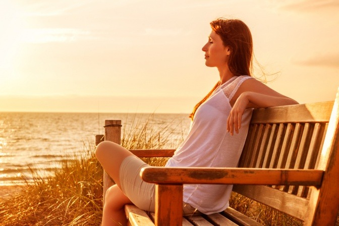 Eine Frau sitzt entspannt auf einer Pank