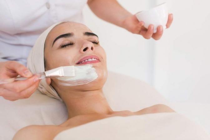 Frau mit Gesichtsmaske im Kosmetikstudio