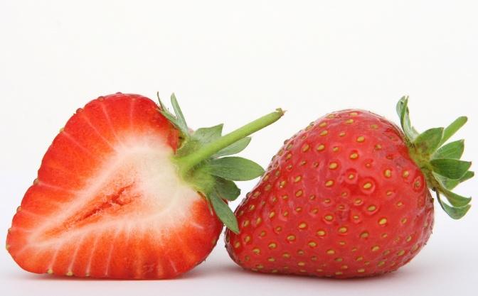 Eine aufgeschnittene Erdbeere liegt neben einer ganzen