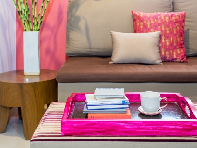 Auf einem erdfarbenen Sofa liegen farbige Kissen