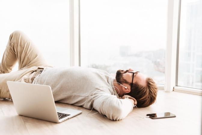 Ein Mann liegt neben seinem Laptop am Boden und hört Musik
