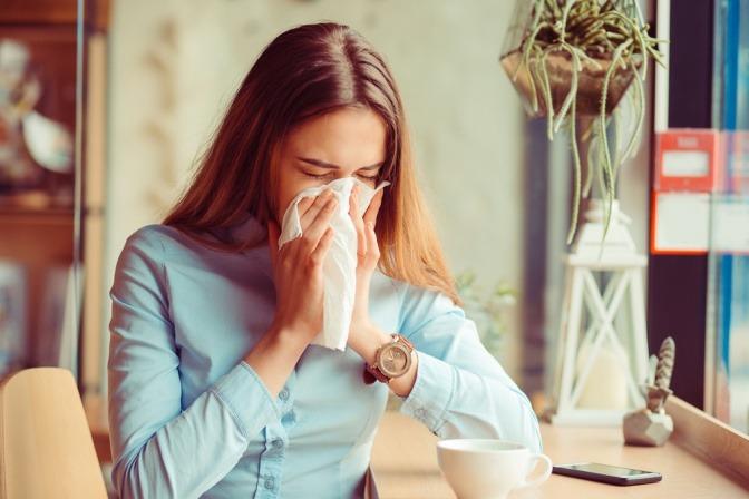 Eine Frau hat eine Erkältung und Schnupfen