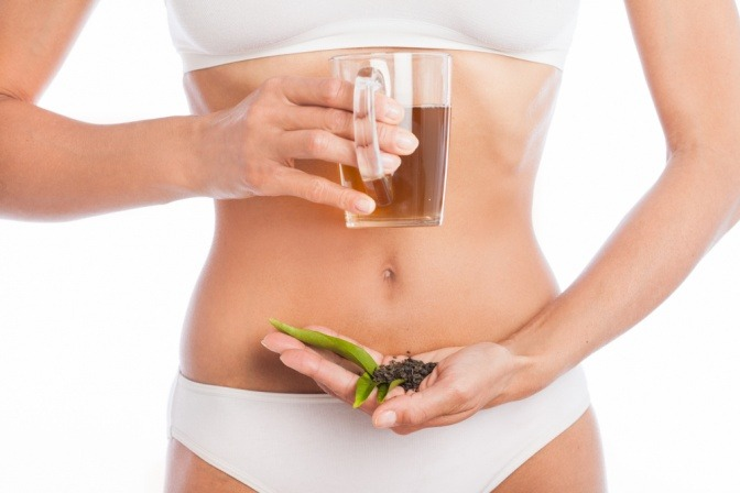 Frau mit Teekanne vor dem Bauch als Ernährung gegen Akne