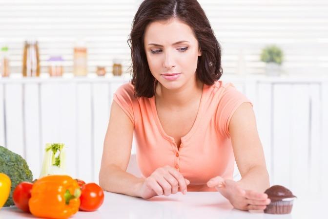 Eine Frau schiebt bei Ihrer Ernährung in der Schwangerschaft Süßes weg