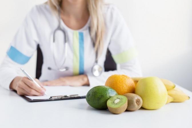 Eine Ernährungsexpertin sitzt vor einem Obstteller und schreibt etwas auf