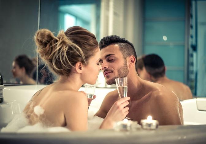 Ein Mann und eine Frau sitzen mit einem Glas in der Badewanne und küssen sich