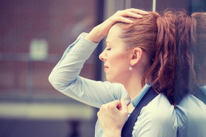 Eine Frau lehnt an einer Wand und greift sich erschöpft an den Kopf