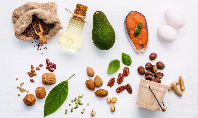 Diverse konzentrationsfördernde Lebensmittel wie Avocados und Nüsse liegen auf einer weißen Oberfläche.