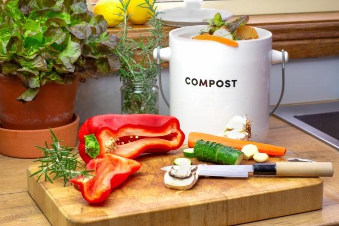 Lebensmittelabfälle auf einem Schneidebrett neben einem kleinen Kompost-Behälter.