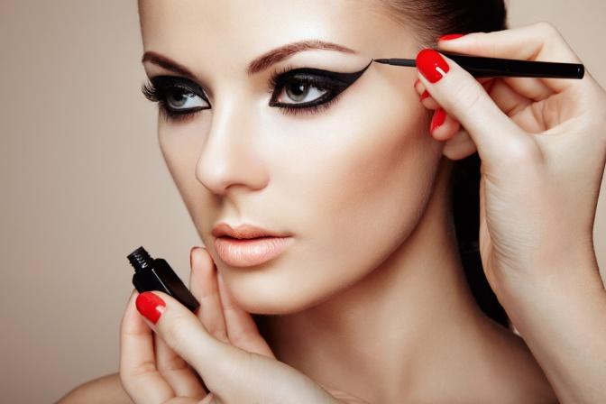 Eine Frau wird mit Eyeliner geschminkt