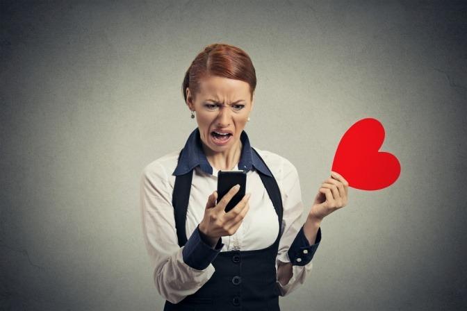 Eine unzufrieden und schockiert wirkende Frau liest Nachrichten auf ihrem Smartphone und wirft ein rotes Plüschherz weg.