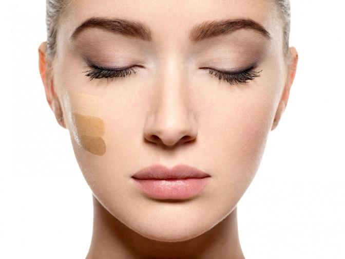 Eine Frau hat verschiedene Farbnuancen einer Creme im Gesicht