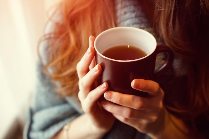 Frau hält Teetasse in Händen als Zeichen für Fasten