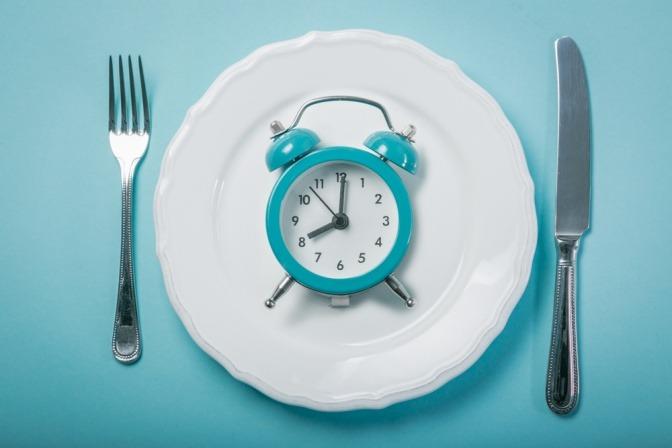 Uhr auf einem Teller als Symbol für imeritiertes Fasten