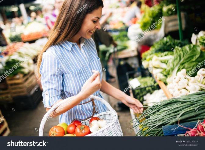 Frau kauft Gemüse auf Markt.