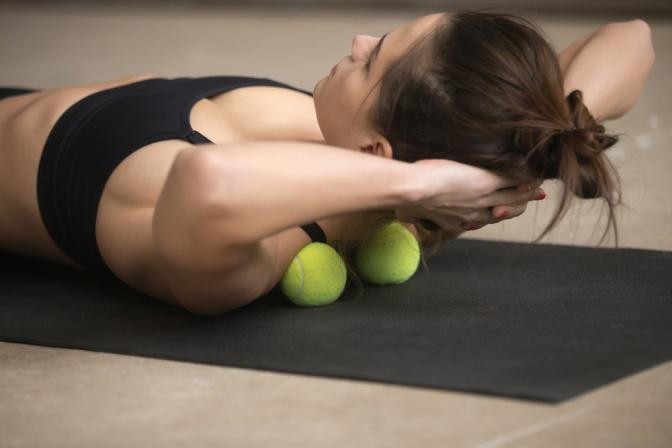 Frau liegt am Boden auf zwei Tennisbällen