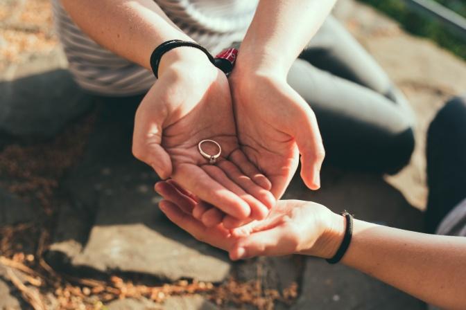 Eine Frau gibt ihren Ehering an ihren Mann zurück.