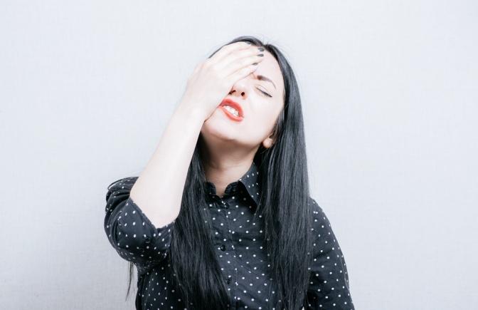 Eine Frau, die aus Fehlern lernen will, bedeckt ihr Gesicht schamvoll mit den Händen.