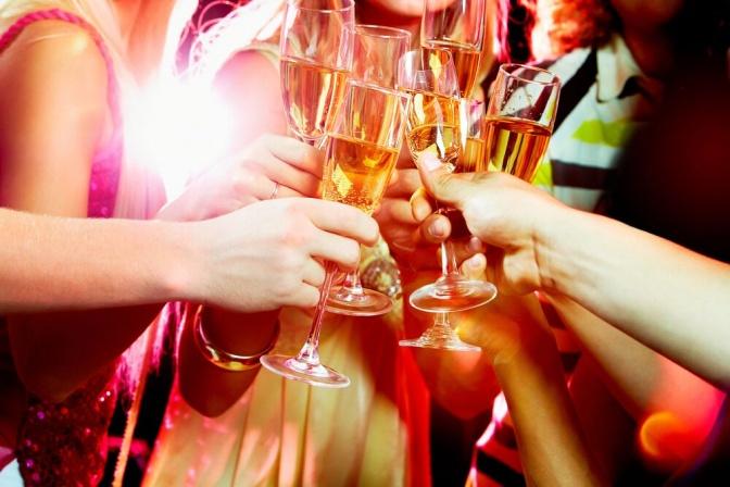 Freunde stoßen feierlich mit einigen Gläsern Sekt an