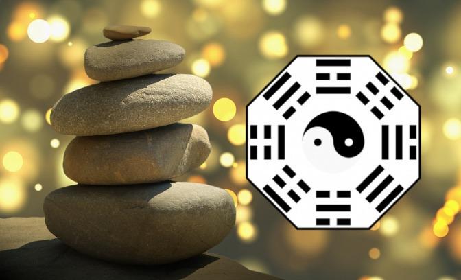 Ein Feng Shui Bagua ist auf einem Hintergrund mit Steinen in Balance