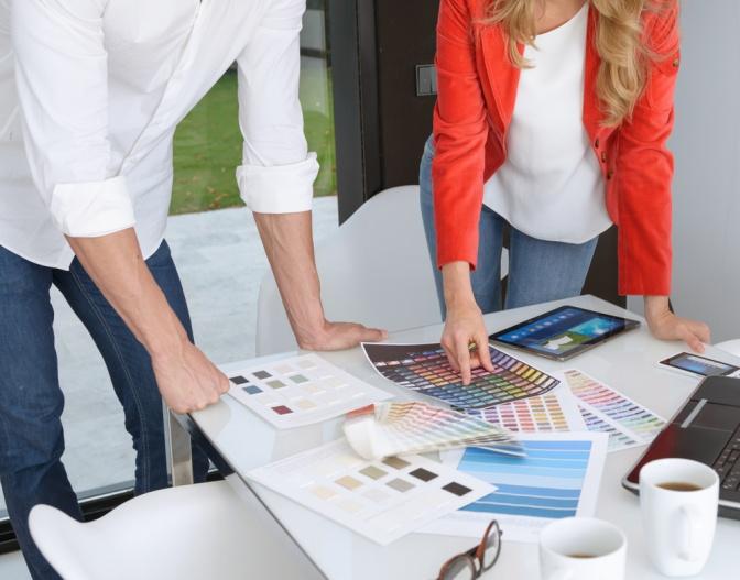 Ein Mann und eine Frau wählen Farben aus einem Farbkatalog aus