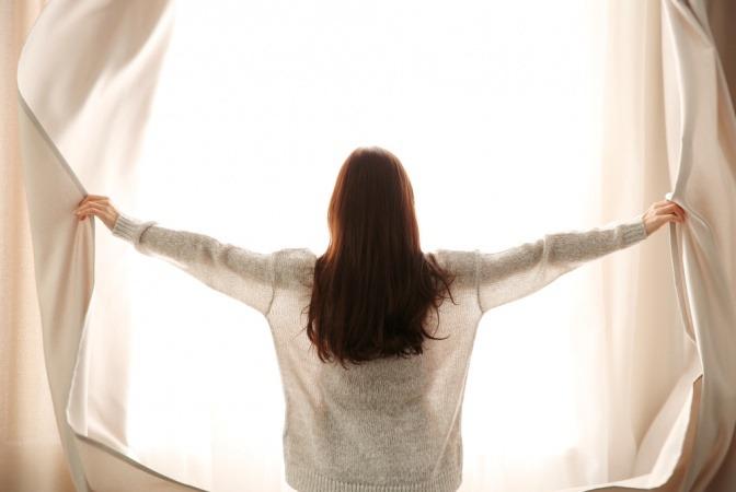 Frau zieht Vorhänge auf