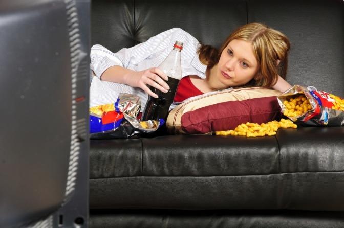 Eine Frau liegt mit ungesundem Essen vor dem Fernseher