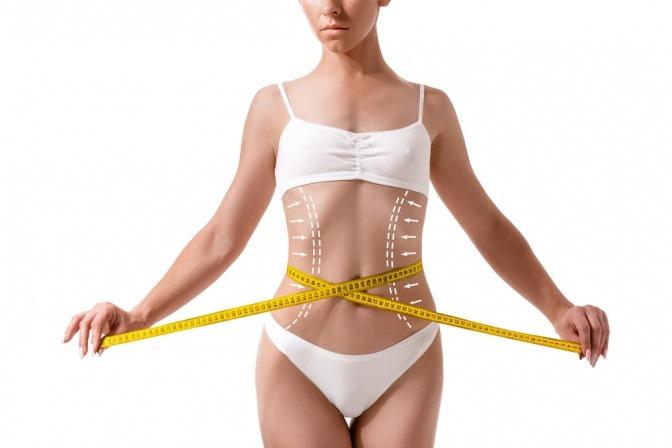 Eine Frau in weißer Unterwäsche vor einem neutralen Hintergrund hat Markierungen für eine Fettabsaugung an den Seiten ihres Körpers und hält die Enden eines um ihre Hüfte gelegten Maßbands mit ihren Fingern fest.