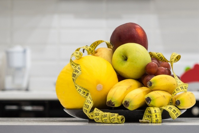 Ein Maßband liegt um Obst, welches gut ist zum Fettverbrennung ankurbeln)