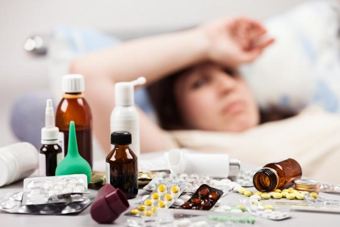Vor einer Frau mit Fieber liegen viele Medikamente