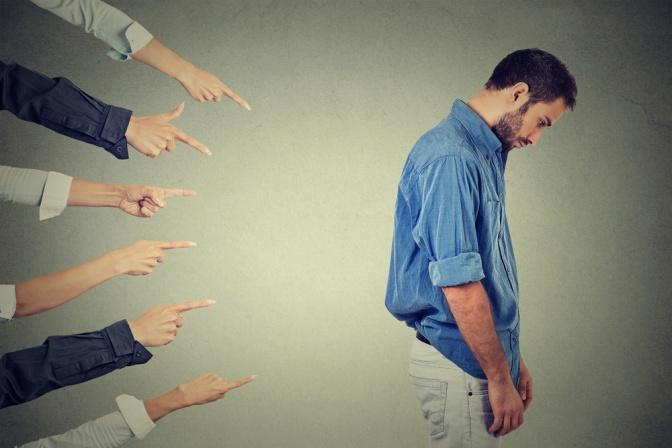 Viele Finger zeigen auf einen gebückten Mann