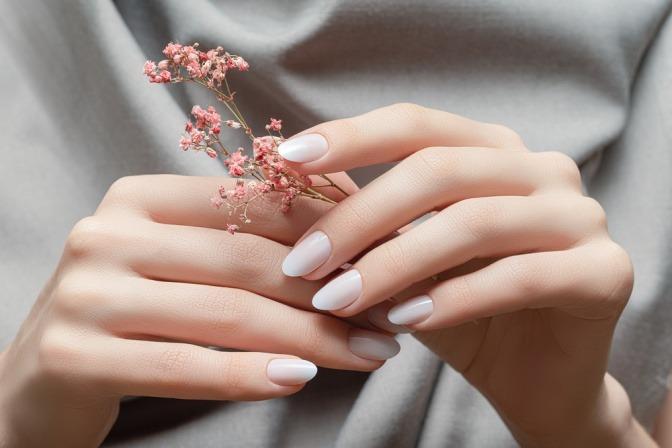 Gepflegte und weiß lackierte Frauenhände halten rosafarbene Blumen