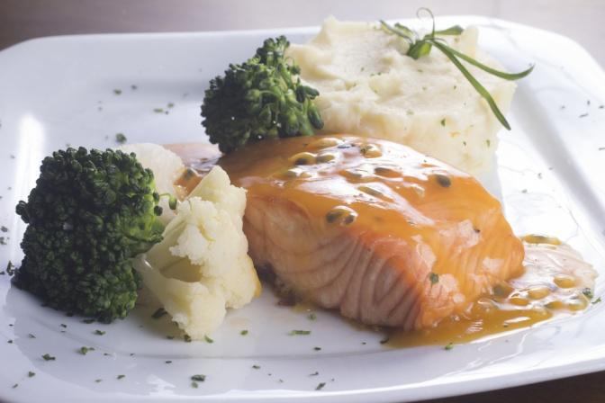 Ein weißes Teller, auf dem Lachs und Gemüse sind, ist abgebildet. Der Lachs ist mit einer Sauce übergossen.