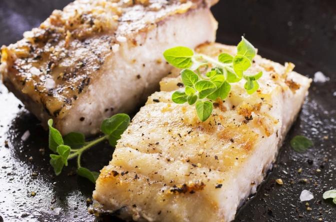Fisch mit Gemüse ist auf einem weißen Teller abgebildet. Auf dem Fisch liegen zwei Zitronenspalten.