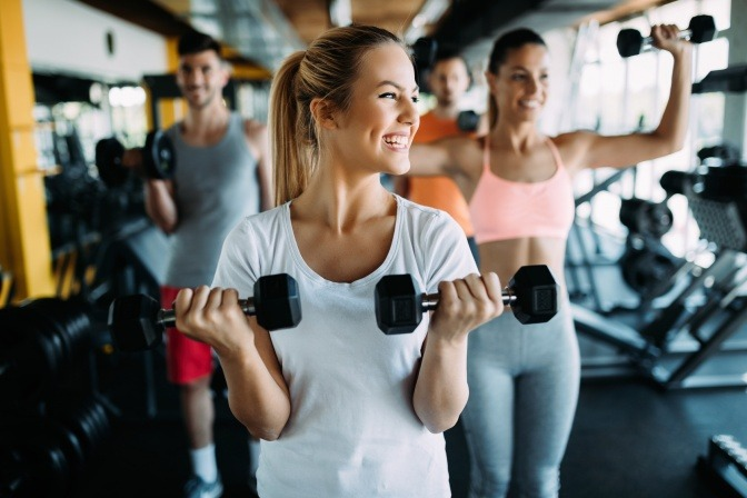 Eine Frau im Fitnesscenter hält Hanteln