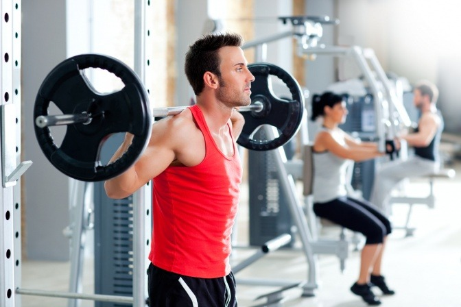 Ein Mann im Fitnessstudio fragt sich wie lange muss ich trainieren um Muskeln aufzubauen