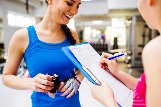 Eine Fitnesstrainerin mit einer Checkliste