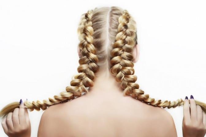 Eine blonde Frau hat zwei geflochtene Zöpfe