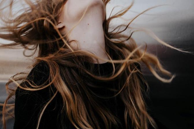 Die langen dunkelblonden Haare einer Frau fliegen in alle Richtungen