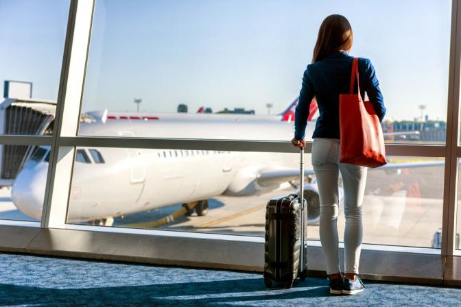 Frau steht am Flughafenterminal