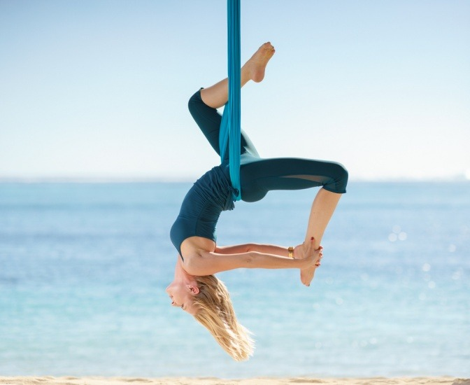 Eine junge Frau betreibt Flying Yoga am Meer