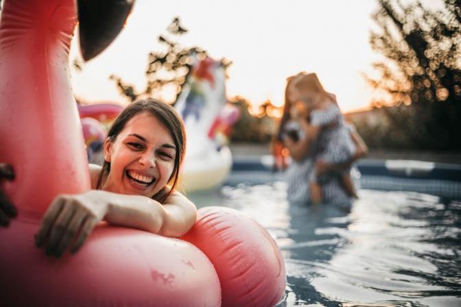 Ein Mädchen schwimmt auf einem Einhorn im Pool