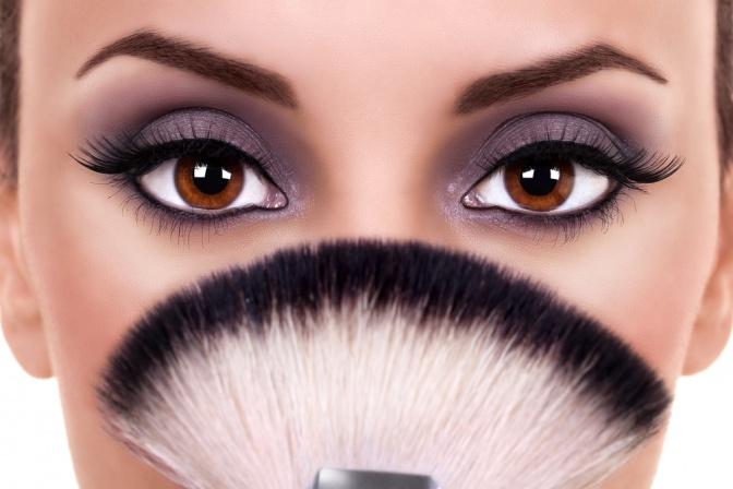 Eine Frau mit dunklen Augenbrauen und einem Fächer vor dem Gesicht