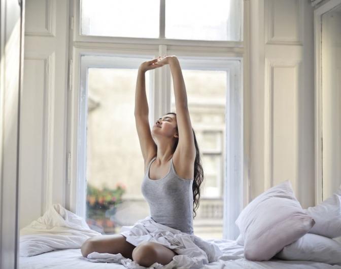 Eine Frau sitzt in ihrem Bett und streckt sich