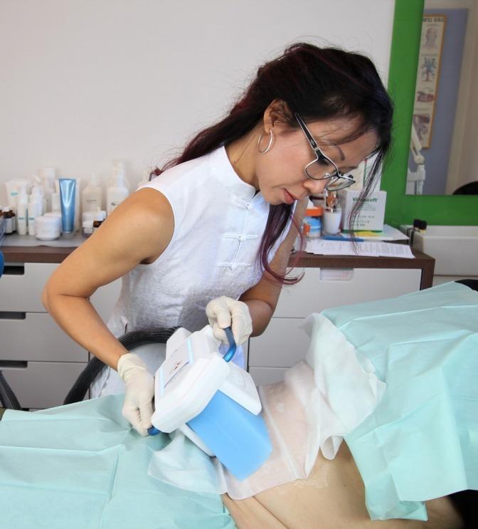 Eine Frau während einer Kryolipolyse-Behandlung