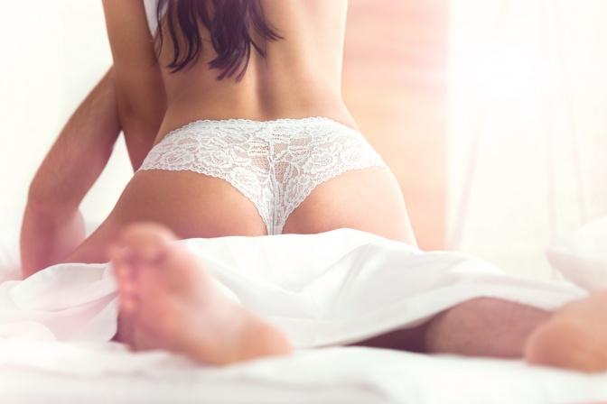 Eine Frau in Rückenansicht ist im Bett beim Sex