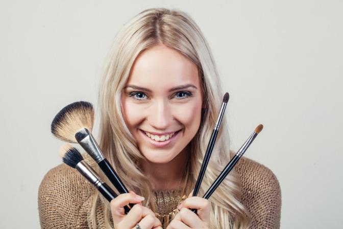 Um das Gesicht einer Frau herum befinden sich verschiedene Pinsel
